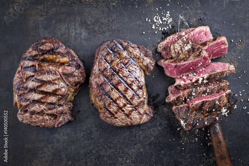 Fotobehang Grill / Barbecue Tree Barbecue Wagyu Entrecote Steaks as top view on old Metall Sheet