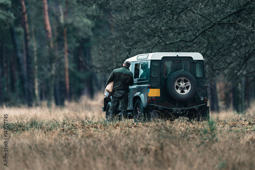 Fotomural  Ranger with jeep in field near forest. National Park Hoge Veluwe.