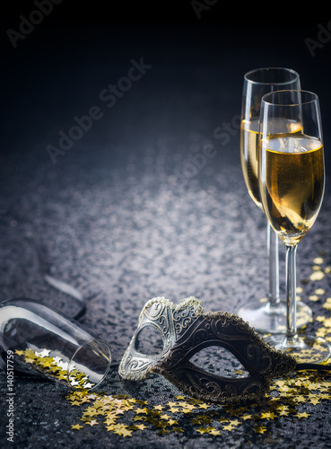 mask and champagne with star shaped confetties
