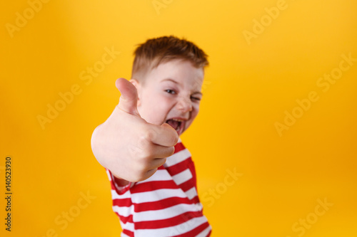 Photo Portrait of a smiling active little boy showing thumbs up