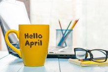 Hello April Greeting Written On Yellow Morning Coffee Or Tea Cup. Spring Time Concept At Office
