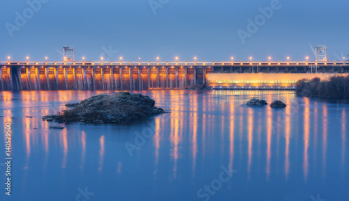 Montage in der Fensternische Damm Dam at night. Beautiful industrial landscape with dam hydroelectric power station, bridge, river, city illumination reflected in water, rocks and sky. Dniper River, Zaporizhia, Ukraine.