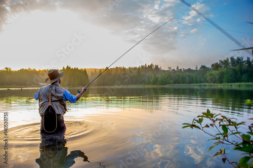 Obraz Young man flyfishing at sunrise - fototapety do salonu