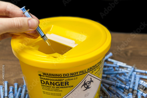 Fototapeta  Needles being put ito a sharps bin