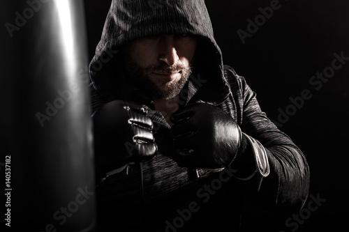 Plakat Studio strzał męski bokser uderza pięścią bokserską torbę.