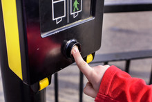 Close Up Of Young Boy Pressing Button To PELICON Crossing. He Is Waiting For The Green Man To Flash Before Crossing The Road