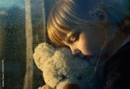 Sad child hugs a plush toy at rainy window. © itsmejust