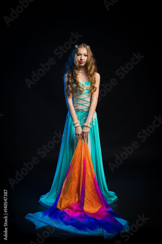 a5bfee688e5 Portrait of a young girl with long hair in a turquoise costume oriental  dancer with a multicolored shawl posing and dancing on a black background  in the ...