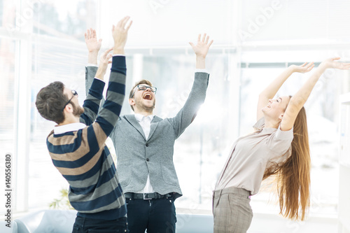 Fototapeta  concept of victory - the jubilant business team standing in a circle, hands up in rejoice success