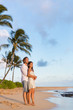 Relaxing couple watching sunset on beach vacation. Multiracial people enjoying tropical holidays together hugging in love.