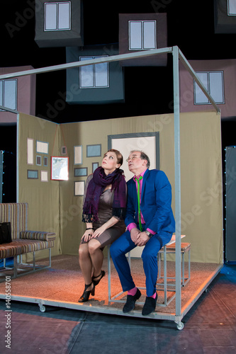 Fototapety, obrazy: Two actors, brunette woman in a brown dress and a man in a pink shirt and blue suit, playing the role on stage