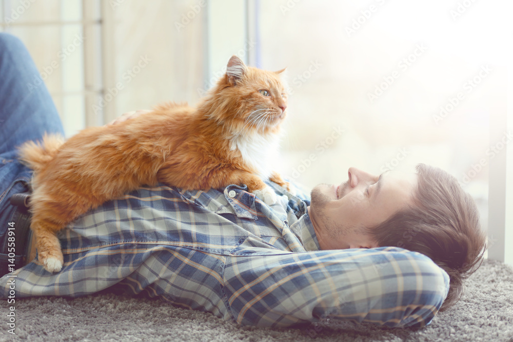 Fototapeta Young man with fluffy cat lying on a carpet