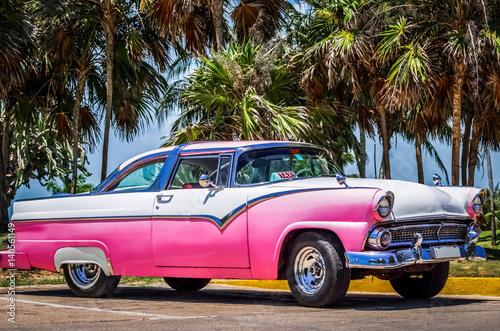 HDR -  Weiß rosa amerikanischer Oldtimer parkt unter Palmen nahe des Strandes in Canvas Print