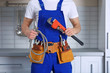 Handsome young plumber in kitchen, closeup