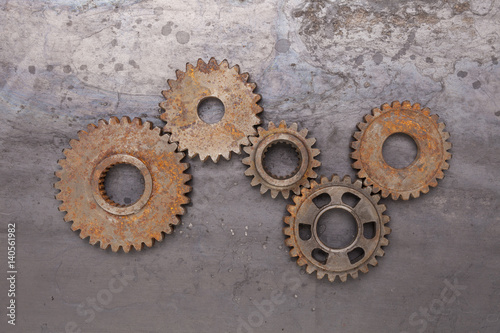 Photo  A group of five rusty gears linked together over a grungy steel background