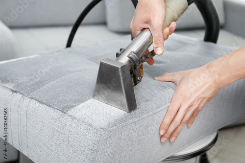 Fotografía  Dry cleaner's employee removing dirt from furniture in flat, closeup
