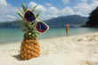 The pineapple on sandy shore. The pineapple with sunglasses placed on a shore with a person walking after. Horizontal outdoors shot.