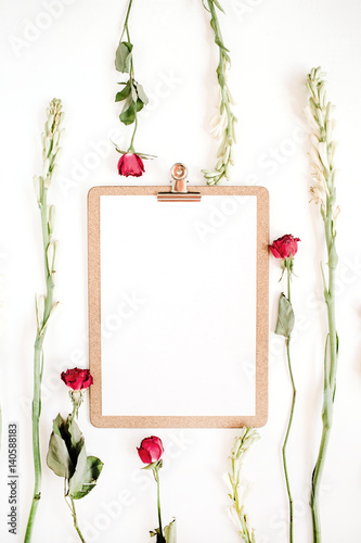 Red roses and white flowers frame with clipboard on white background ...