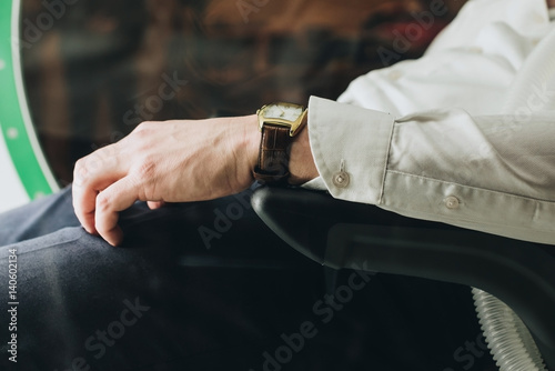 Hand on the arm of a man sitting in a chair Wallpaper Mural