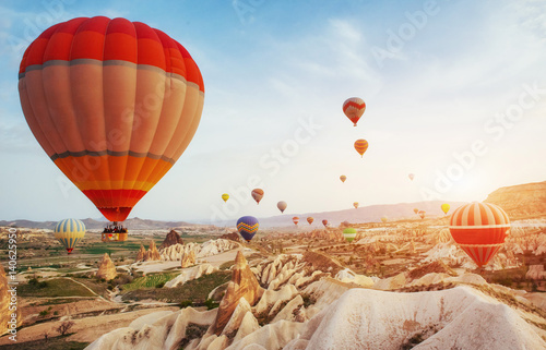 Hot air balloon flying over rock landscape at Turkey. Cappadocia