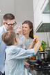 Happy family preparing spaghetti in kitchen