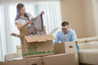 Mid-adult couple unpacking cardboard boxes in new home