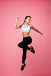 Fit girl jumps holding left hand back pointing with finger