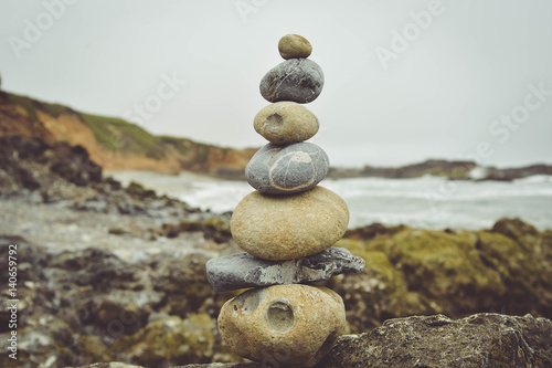 Stacked stones on rocks at beach against sky
