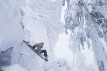 Side View Of Woman Sliding On Wooden Plank At Snow Covered Mountain