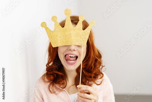 Fototapeta frau versteckt sich hinter eine goldenen krone