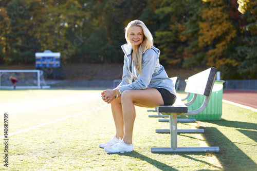 A Teenage Girl Sitting On The Bench At Soccer Field