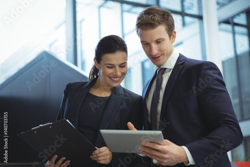 Fotografía Business executives discussing over digital tablet on stairs