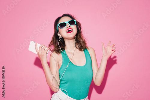 Plakat Letnia pani. Piękna azjatykcia dziewczyna z fachowym makeup i eleganckim fryzura śpiewem, tanem i podczas gdy słuchający muzyka na różowym tle.