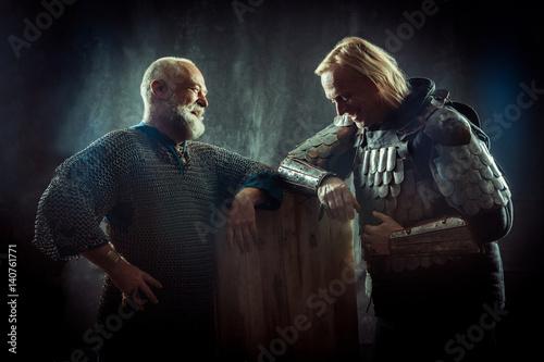 Plakat Dwóch potężnych rycerzy odpoczywających w tawernie. Ciemne tło.