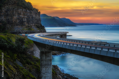 Spoed Fotobehang Australië Sunset over the Sea cliff bridge along Australian Pacific ocean coast with lights of passing cars