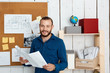 Young successful architector smiling, holding drawings, standing in office background.