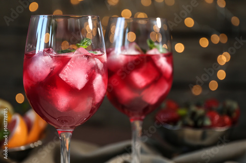 Fototapeta  Glasses of delicious wine spritzer on blurred lights background