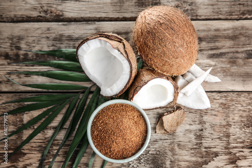 Foto auf Leinwand Palms Bowl of brown sugar and coconut on wooden background