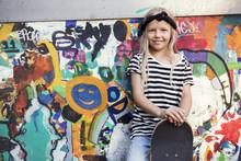 Portrait Of Smiling Girl Holding Skateboard While Standing Against Graffiti Wall