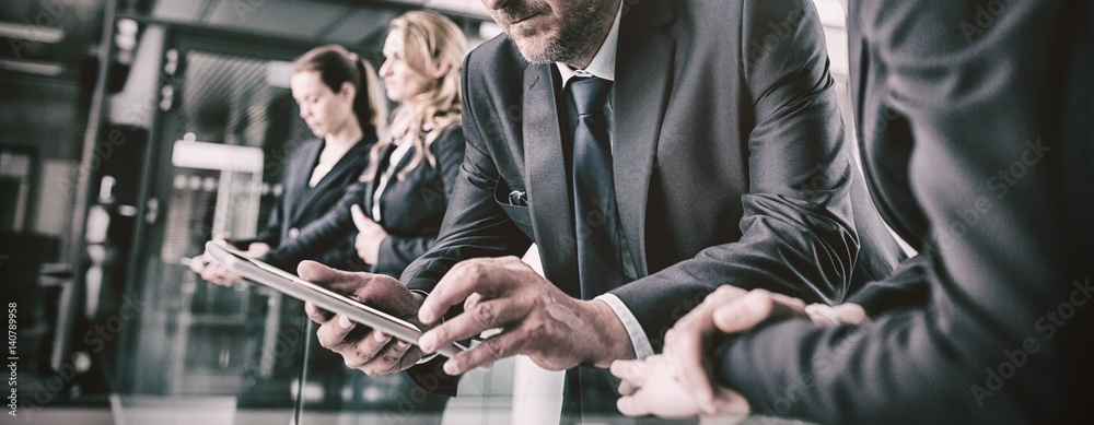Fototapeta Businessman with colleague using digital tablet