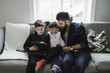 Father and sons watching tablet on sofa