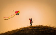 Woman Flying Kites On The Mountain With Sunset.