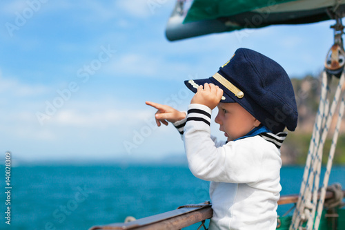 Valokuva  Funny little baby captain on board of sailing yacht watching offshore sea on summer cruise