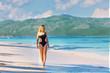 young beautiful girl in black swimwear in full growth walking on the blue beach