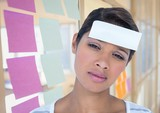 Fototapeta Sypialnia - Upset woman with blank note on forehead in office