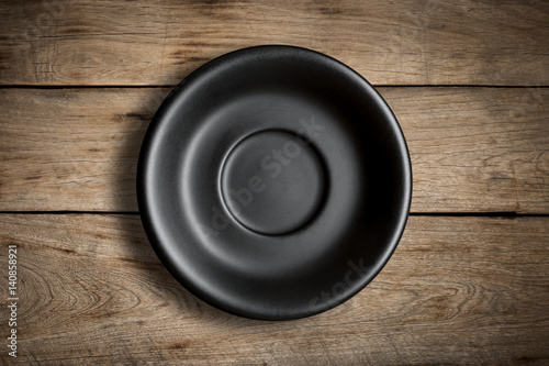 Poster de jardin Vache Top view of blank black dish on a wood background.