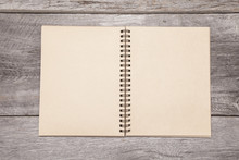 A Blank Recycled Paper Scrapbook Sits On A Rustic Wooden Background.