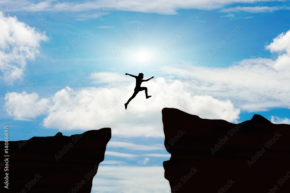 Fototapeta Man jump through the gap between hill.man jumping over cliff on sunset background,Business concept idea