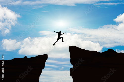 Fototapeta Man jump through the gap between hill.man jumping over cliff on sunset background,Business concept idea obraz