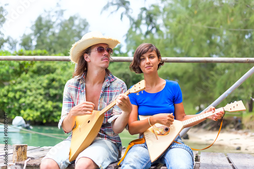 Happy people playing music at wooden pier at river background